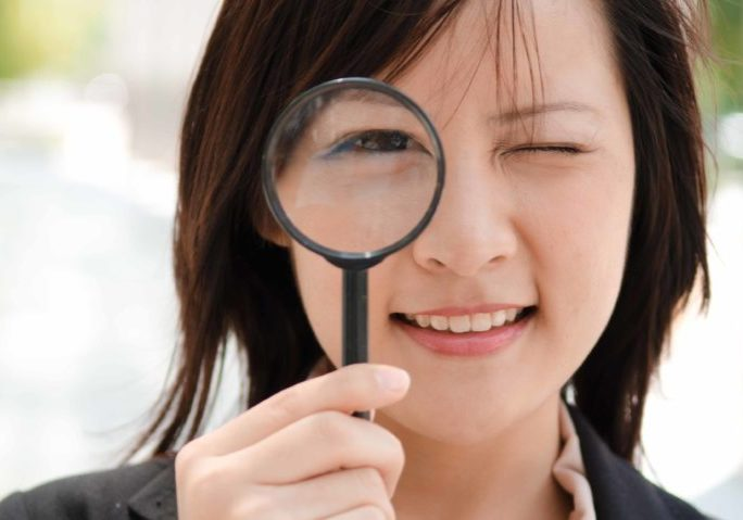 asian business girl with magnifying glass, smiling